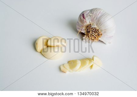 Fresh raw garlic whole cloves, slices and half head of unpeeled garlic on white background