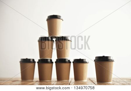 One cup presented in focus in front of craft cardboard take away paper cups with black caps in pyramid house shape isolated on handmade pallet wooden table