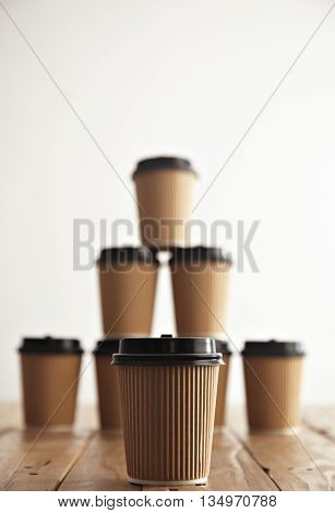 One cup presented in focus in front of craft cardboard take away paper cups with black caps in pyramid house shape isolated on handmade pallet wooden table, close view