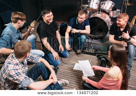 Musicians learning new song on the floor. Top view on music band members sitting on the floor with song text. Vocalist smiling at woman. Lifestile of young people group. Teamwork.