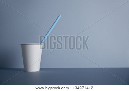 One take away white paper cup without cap with blue drinking straw inside presented in left side, isolated on gray