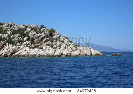 Stone Mountain with green bushes down to the sea. Next to a small island. Blue sky and blue waves on the pure water.