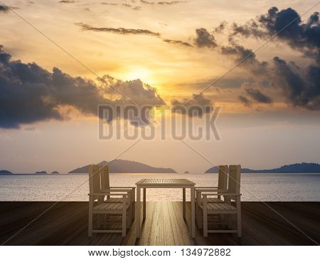 Wooden terrace with dining table and chairs on tropical ocean view in sunset