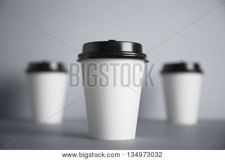 Three take away white paper cups with closed black caps, top view, isolated on center of simple gray background, first cup in close focus, cups behind are unfocused in bokeh