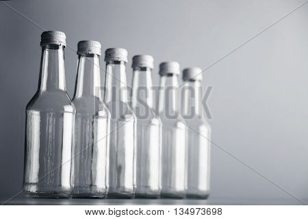 Set of unlabeled empty transparent bottles with dynamic focus isolated in row line on side on simple gray background