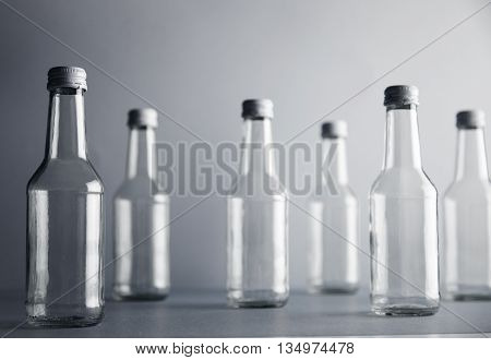 Set of empty cristal unlabeled bottles randomly presented on gray surface, isolated, close focus frontal bottles