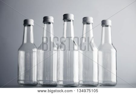 Clear unlabeled transparent bottles for cider or alcohol drinks presented in center, closed with metal white caps, isolated on gray background