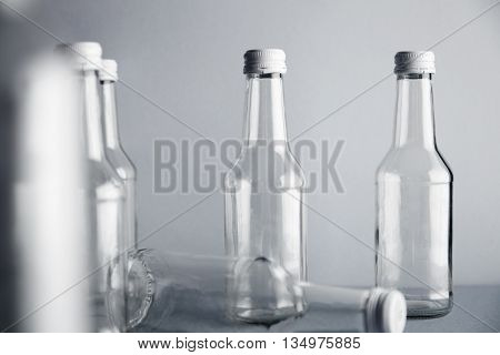 Close focus on empty clear glass bottles isolated on simple gray background, container presentation for retailers