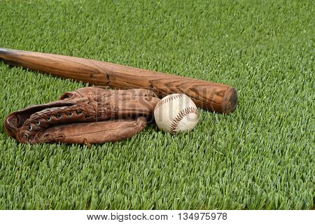 baseball with glove and bat on grass