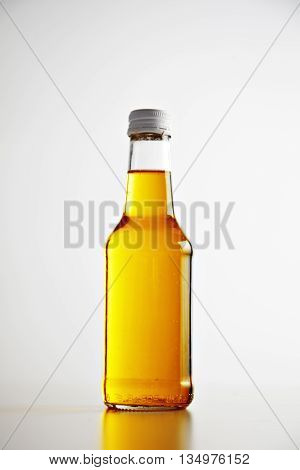 Craft unlabeled bottle closed and sealed with metal cap, with beer cocktail inside presented on white isolated