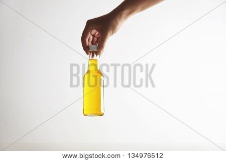 Hand holds closed rustic glass bottle with tasty cold drink inside, isolated on white in center