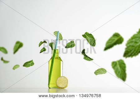 Fresh lime herbal drink inside transparent cocktail opened bottle with blue drinking straw inside, lemon slice near and green mint leaves flying around in air, isolated on white commercial