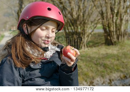 pretty preteen with roller skate helmet eat an apple