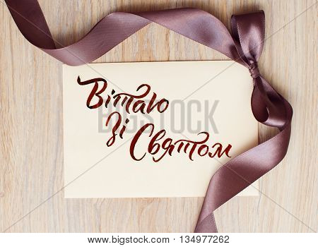 close up of card note with brown ribbon on white background and words happy holiday on Ukrainian.