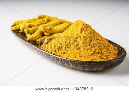 dry turmeric powder with dry turmeric, selective focus