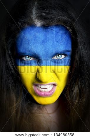 Soccer fan with Ukraine flag painted over face