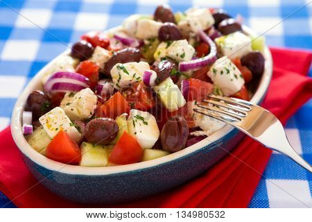 Close up of greek salad with feta cheese olives tomatoes cucumber and onions over a checkered tablecloth
