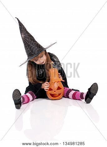 Little girl dressed like witch for Halloween party with pumpkin. Studio portrait isolated over white background.