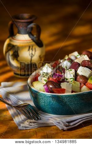 Greek salad with feta cheese tomatoes cucumber olives and onions with greek amphora with a colored background