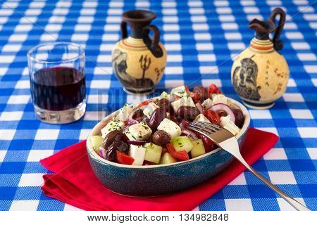 Greek salad with feta cheese tomatoes cucumber olives and onions with red wine and greek amphorae over a checkered tablecloth