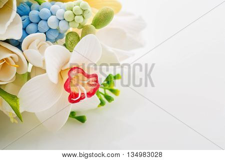 Beautiful handmade art clay spring flower bouquet. Bridal accessory. Over white background. Copy space.