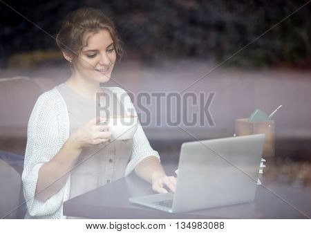 Modern Woman Working On Laptop In Coffee Shop. Shot Through Window