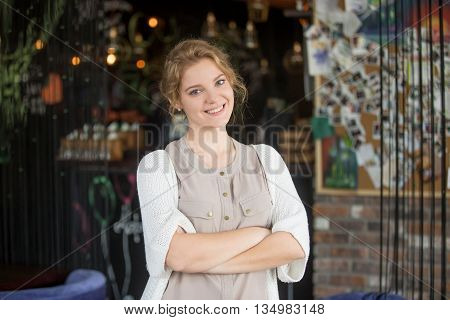 Half-length portrait of young beautiful female standing at her work place with crossed arms. Woman welcoming customers at her own coffee shop. Attractive model posing with arms folded on chest