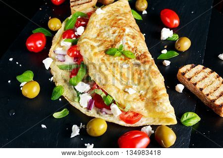 Vegetables Omelette with tomatoes, basil, greek cheese, parmesan, olives, grilled toast on stone board