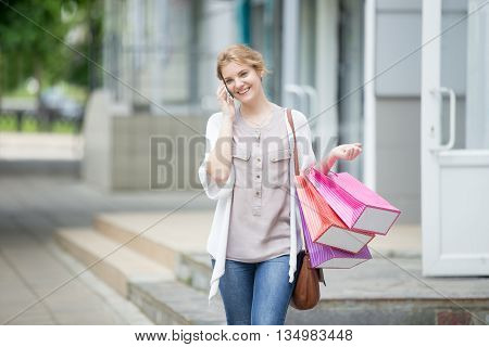 Portrait Of Young Smiling Woman On Mobile Phone During Shopping Time