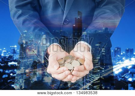 Double exposure of cityscape and businessman collect many coins on hands finance and banking concept