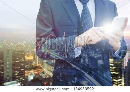 Double exposure of professional businessman using smart phone and blurred city centre of business with trading graph chart Technology & Business trading concept