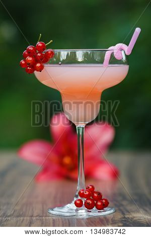 Glass of cold pink cocktail with straw on green background bokeh