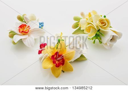 Three beautiful handmade art clay spring flower bouquets. Bridal accessory. Boutonniere. Over white background.