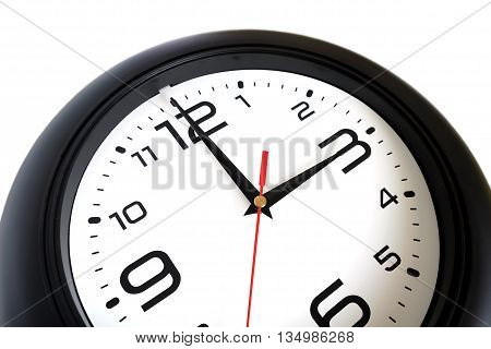 Fragment of big round wall clock, with a black rim isolated on white background close-up and arrows showing three o'clock isolated on white close-up