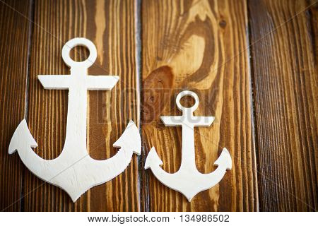 decorative wooden anchor on the wooden background