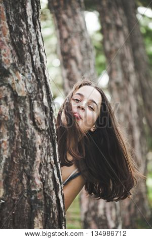 girl making faces behind tree in park