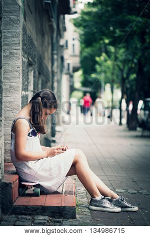 teen girl in white dress sit on skate use smartphone street shot summer day