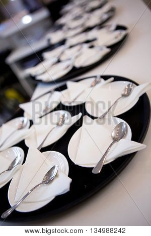 lot white plates, saucers , spoons and paper napkins on a tray for cake, dessert