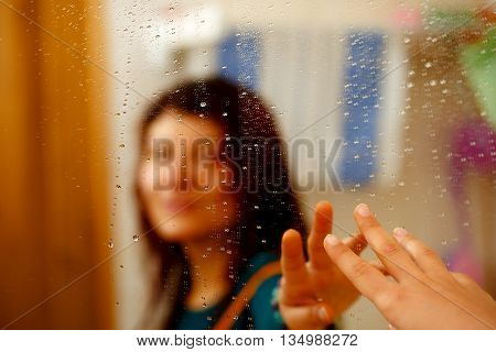 misty reflection of girl in the mirror with water droplets