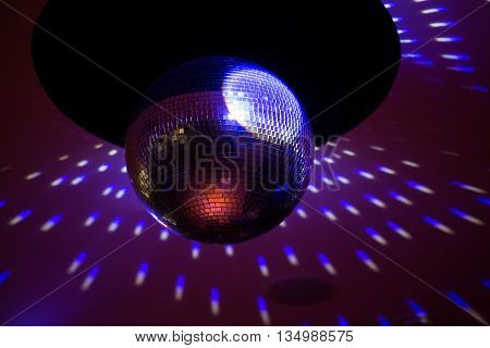 Mirror disco ball with light reflection on the ceiling, on a black background