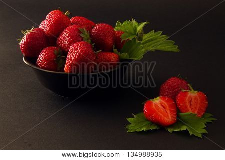 plate of strawberries with leaves and cut strawberry on a dark textural background. Darkened photos.