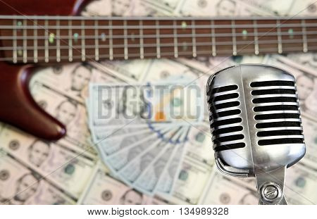 Bass guitar and retro microphone with dollars on money background. Money and music still life concept.