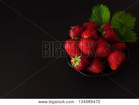 plate of strawberries with leaves on a black background. Blackout photos.
