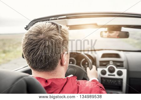 Man driving a convertible cabriolet car on the country road. View from the inside behind the driver.