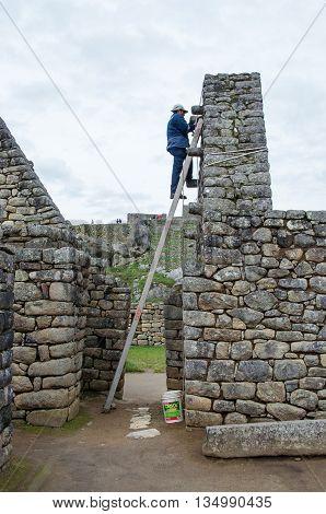 MACHU PICCHU PERU - MARCH 15 2015: Construction worker doing restoration works at Machu Picchu Peru.