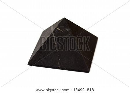 A pyramid of shungite isolated on white background. Shungite Pyramid Mineral. Pyramid made of natural shungite.