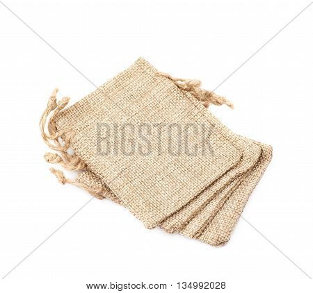 Pile of multiple tiny sackcloth bags with a tie string, composition isolated over the white background