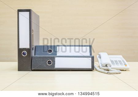 Closeup document file and white phone office phone on blurred wooden desk and wall textured background in the meeting room under window light
