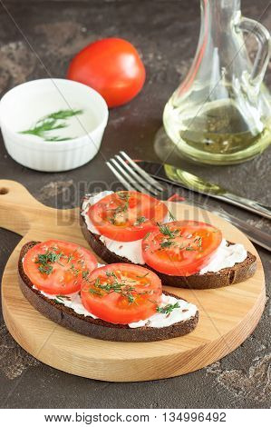 Sandwich with soft cheese and tomatoes on dark bread