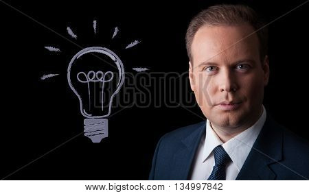 portrait of a businessman with an idea on a black background
